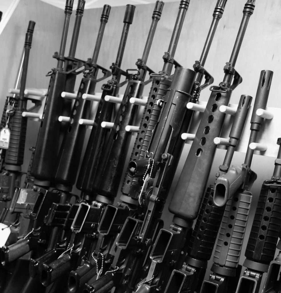 12 black rifles on display rack